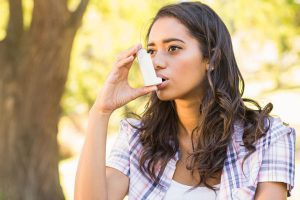 A pretty brunette using an inhaler on a sunny day